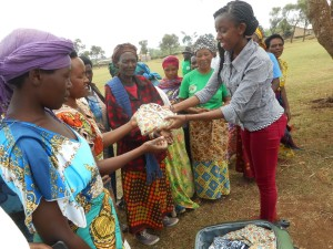 WD4H Business Coordinator, Judy Rwibutso, distributing pads to Ruganeheza  after educating the women in pad use