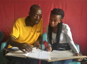 Judy reviewing the books with Genda Ugire Utyo Co-op leader