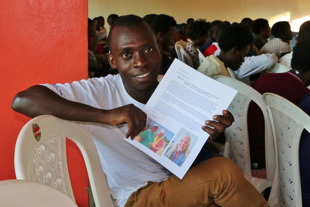 Our sponsors exchange letters several times a year with their students. This is Alphonse with a cherished letter from his sponsor, Jojo.